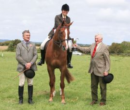Judges Aidan Ryan (left) and Billy Phelan with Laura Kelly after she won the riding horse championship at Bannow Rathangan Show riding her four-year-old home-bred gelding Marley & Me